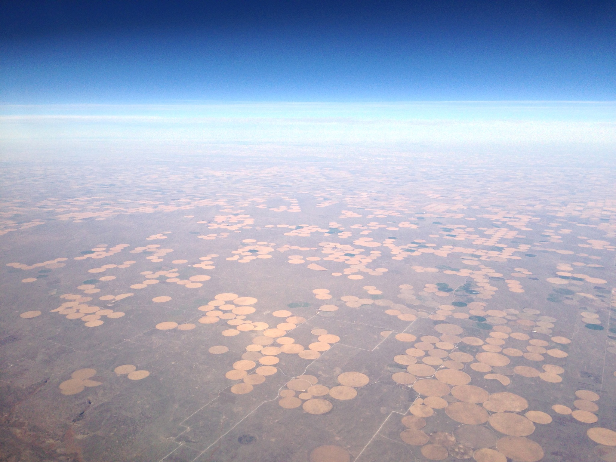 overlooking clusters of circular fields, from high above, toward a distant, blue horizon